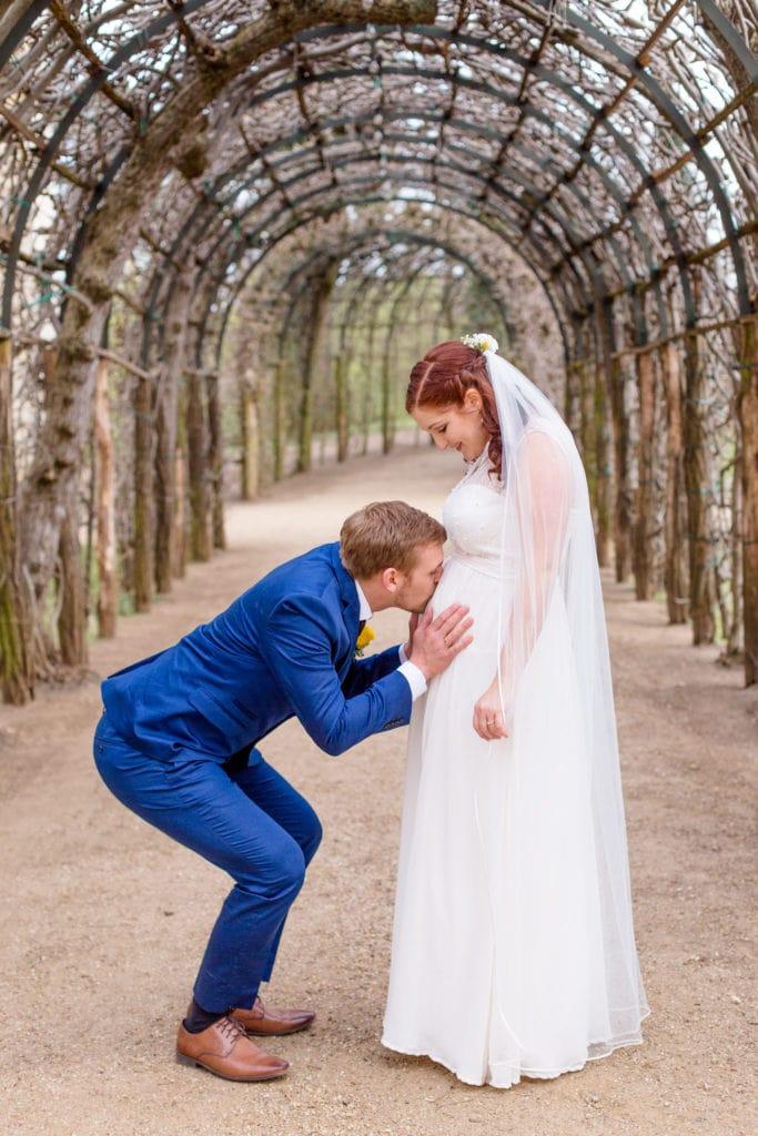 Bräutigam küsst den Bauch seiner schwangeren Braut auf dem Pfingstberg in Potsdam