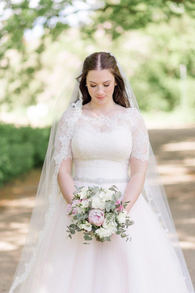 Brautportait mit Brautstrauß im Park