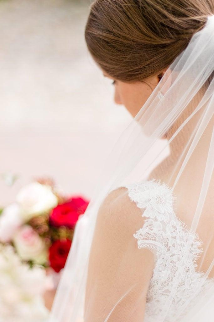 Braut mit Schleier und Brautstrauß mit roten Rosen