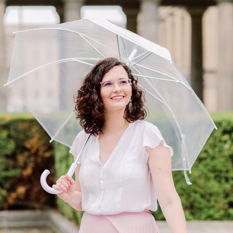 Frau mit brünetten Locken, weißen Shirt und rosa Pliseerock schaut lächelnd zur Seite. In der Hand hat sie einen durchsichtigen Regenschirm.