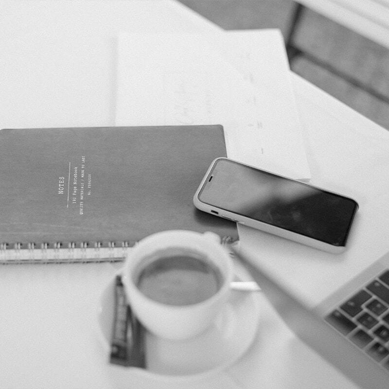 Ein Notizbuch, ein Smartphone, ein Laptop und eine Tasse Kaffee auf einem Tisch in Schwarz Weiß