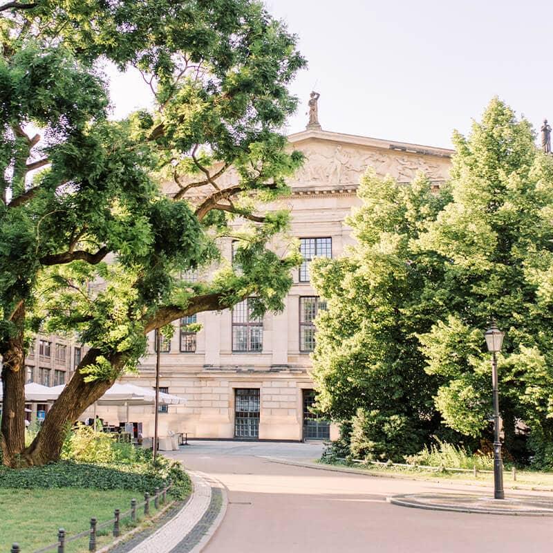 Gendarmenmarkt Berlin. Ein Weg der zu einem Opernhaus in klassischer Architektur führt. Links und Rechts davon Bäume mit grünen Blättern. Die Sonne scheint.