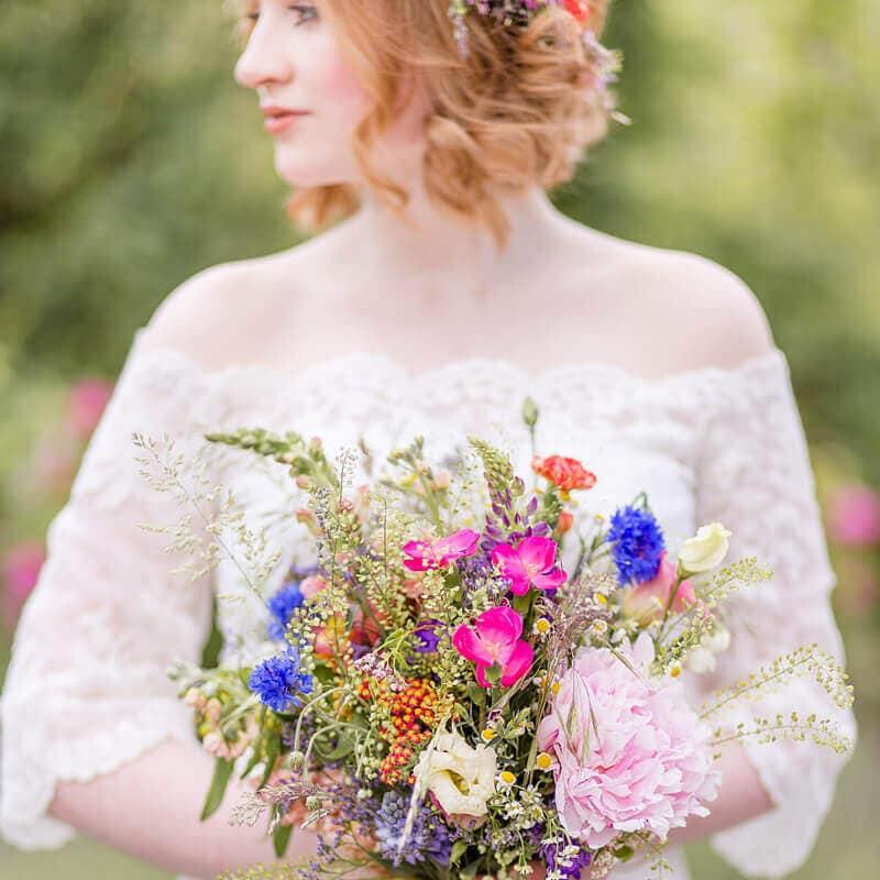 Braut mit Wildblumen Brautstrauß und roten Locken