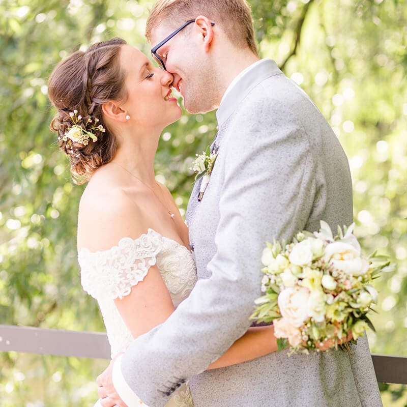 Brautpaar vor Weide, welches sich küsst