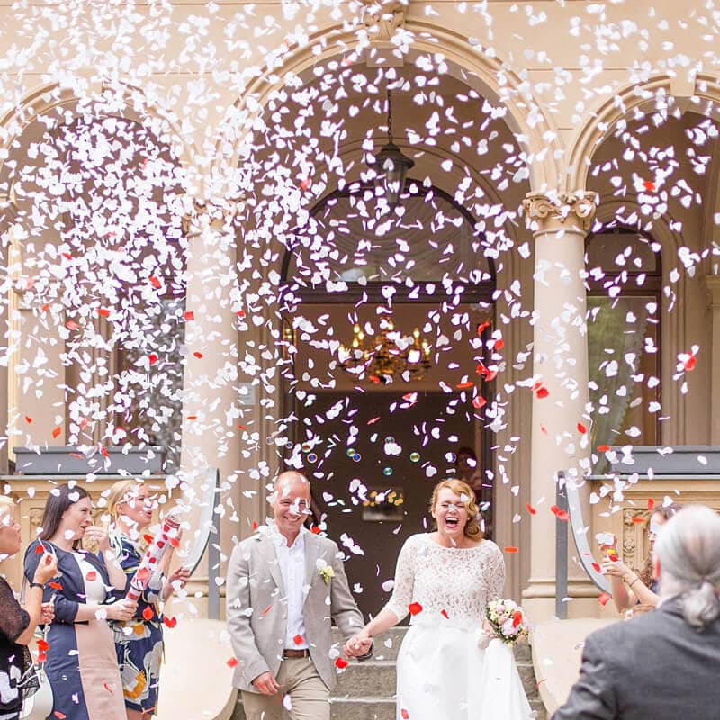 Fröhlich lachendes Brautpaar verlässt Standesamt, um sie herum alles voller Konfetti