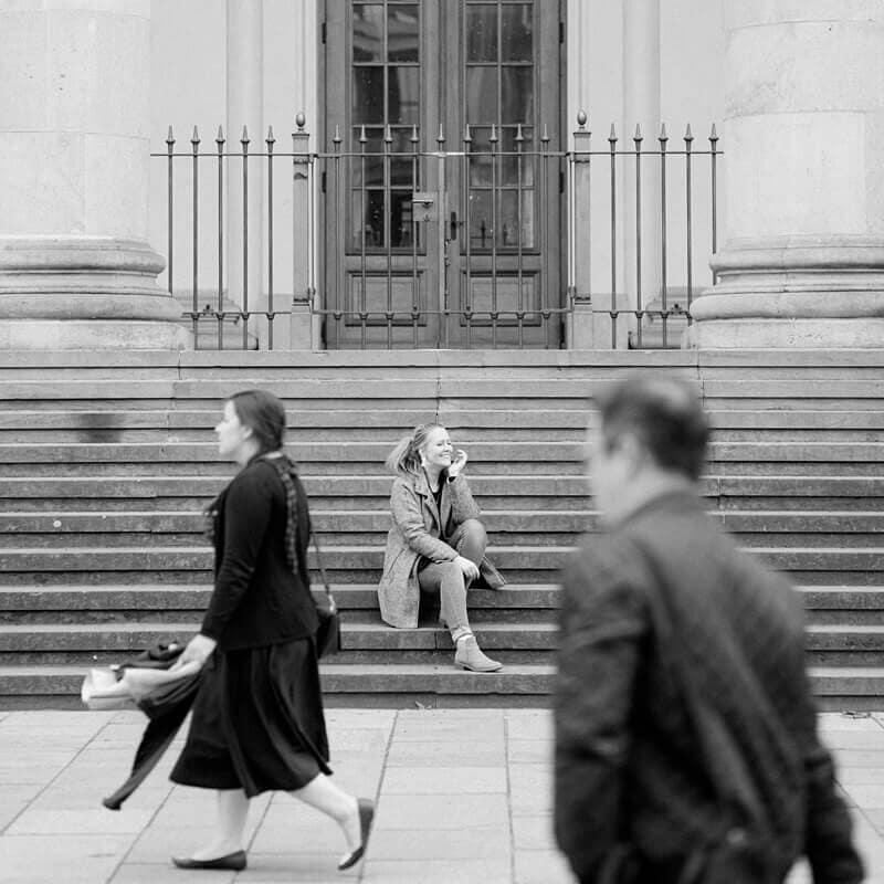 Schwarz Weiß Foto: Frau sitzt auf Treppe, Menschen laufen davor