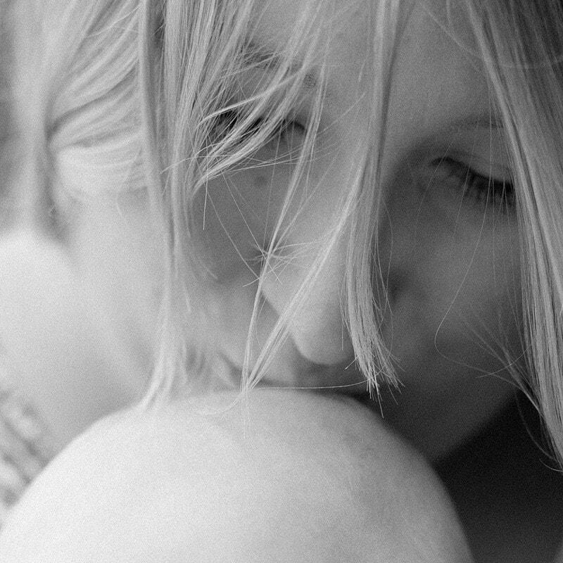 Schwarz Weiß Foto: Mutter küsst Baby auf den Kopf