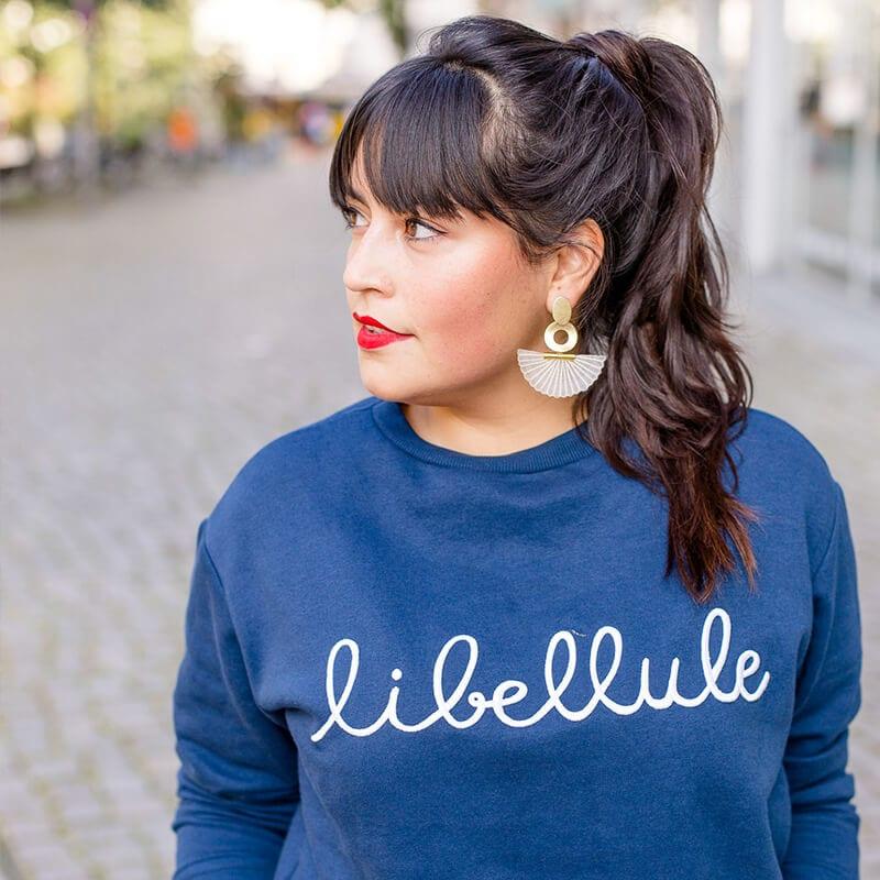 Frau mit blauem Pullover und braunen Haaren schaut nach links