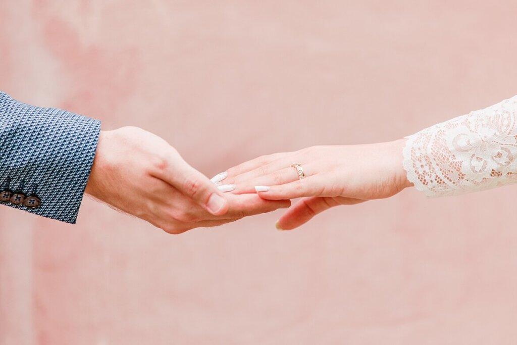 Nahaufnahme von Händen eines Brautpaares, die sich berühren