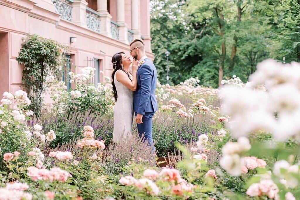 Brautpaar inmitten von Blumen und Rosen