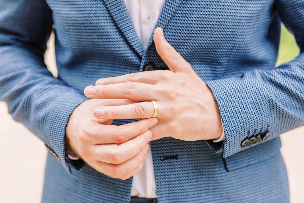 Nahaufnahme Bräutigam steckt sich Ring an den Finger