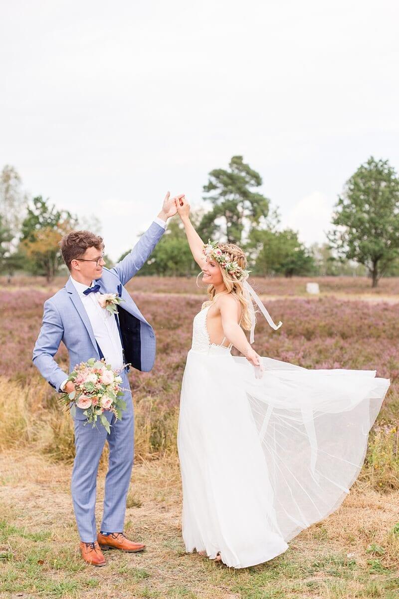 Brautpaar tanzt in der Lüneburger Heide, das Kleid weht im Wind