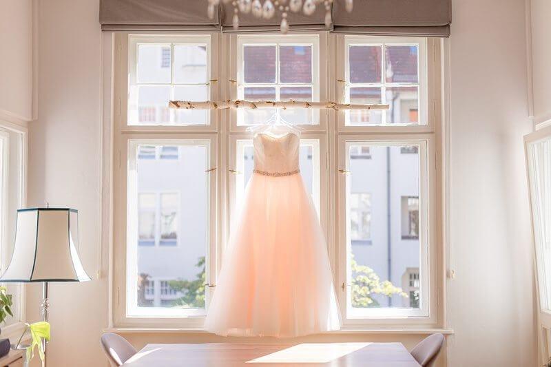 Brautkleid hängt vor Fenster