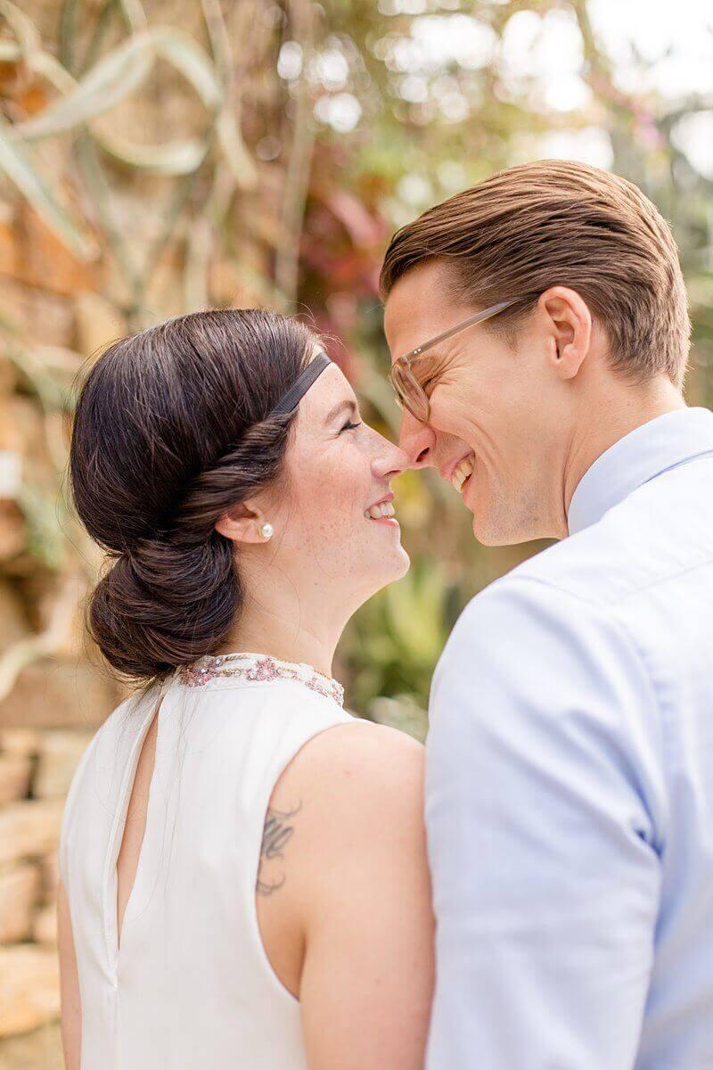 Verliebtes Paar von hinten, was sich beinahe küsst und lacht