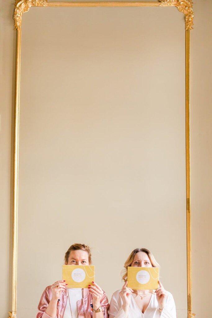 Zwei Frauen halten eine Karte vor ihr Gesicht und schauen darüber hinweg