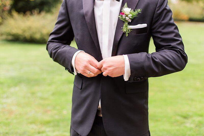 Ausschnitt Bräutigam, wie er seinen Jackettknopf zuknöpft