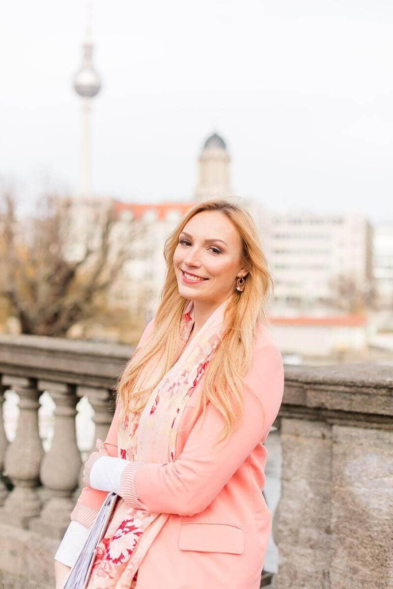 Lächelnde Frau vor Fernsehturm mit lachsfarbenen Blazer