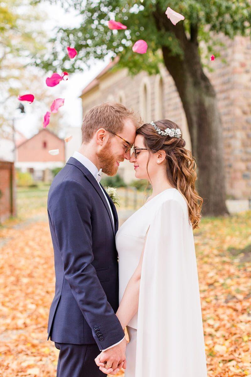 Brautpaar im Herbst mit Rosenblättern um sie herum