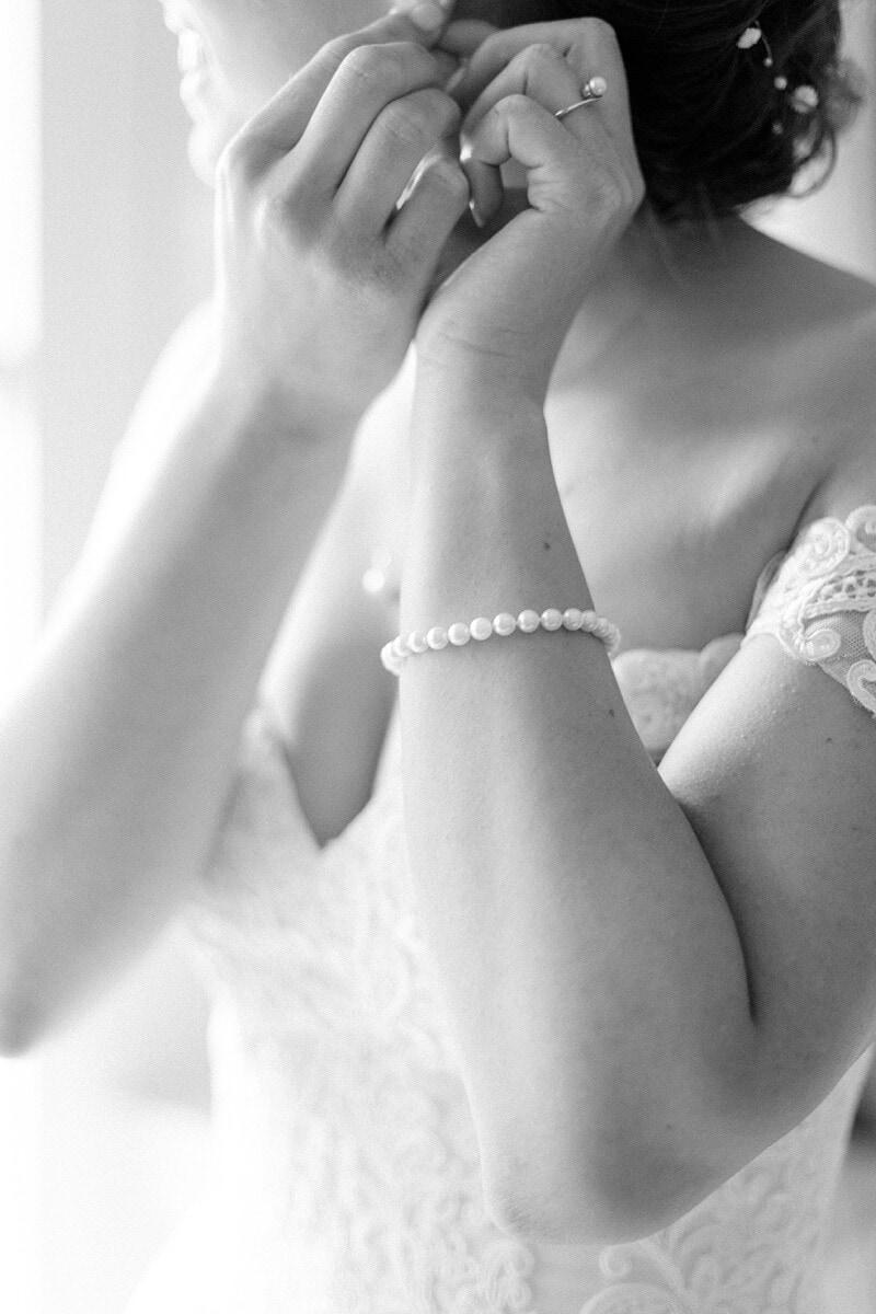 Detailaufnahme einer Braut, die ihren Ohrring einsteckt - Hochzeitsfotograf Berlin - Miriam Kaulbarsch