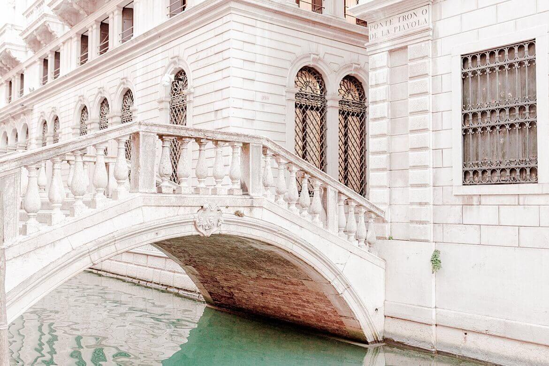 Brücke in Venedig über türkisblauen Kanal umrandet von weißen Gebäuden
