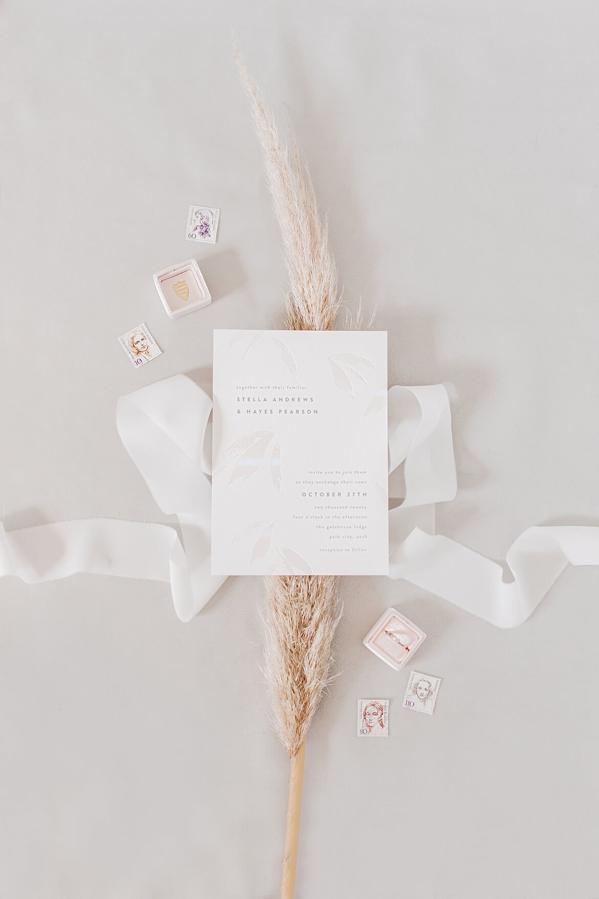 Gestyltes Flatlay mit einer Einladung, Ringbox, Briefmarken, Seidenband und einer Trockenblume