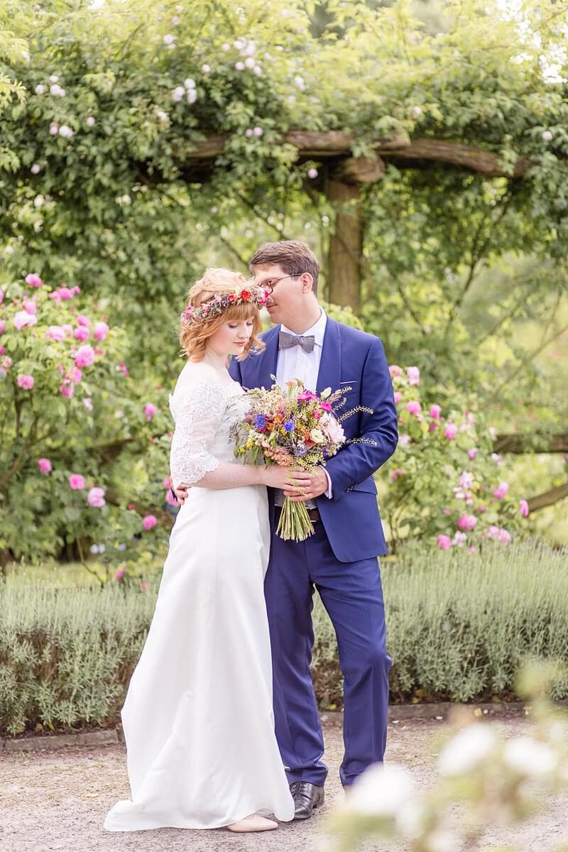 Brautpaar umringt von Rosen im Park