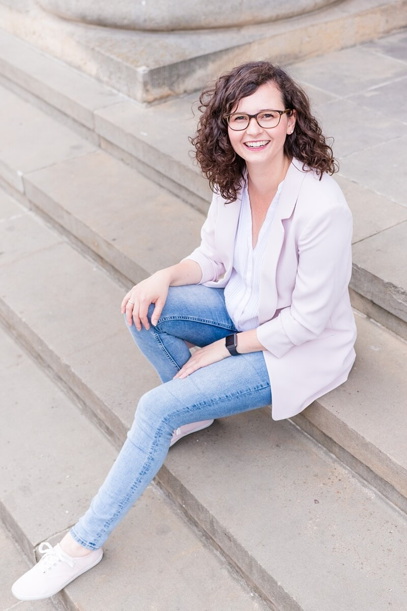 Frau im rosa Blazer und Jeans sitzt auf Treppe und lächelt in die Kamera