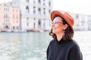 Lächelnde Frau mit Hut schaut auf Kanal in Venedig