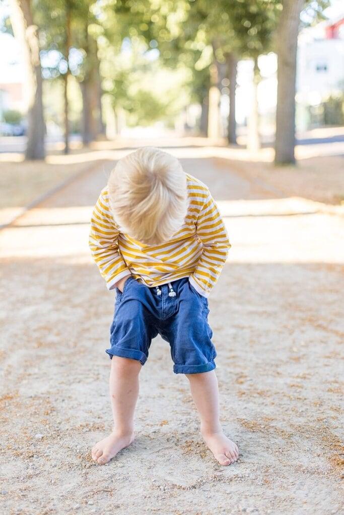 Kleiner Junge guckt an seinen Beinen herunter