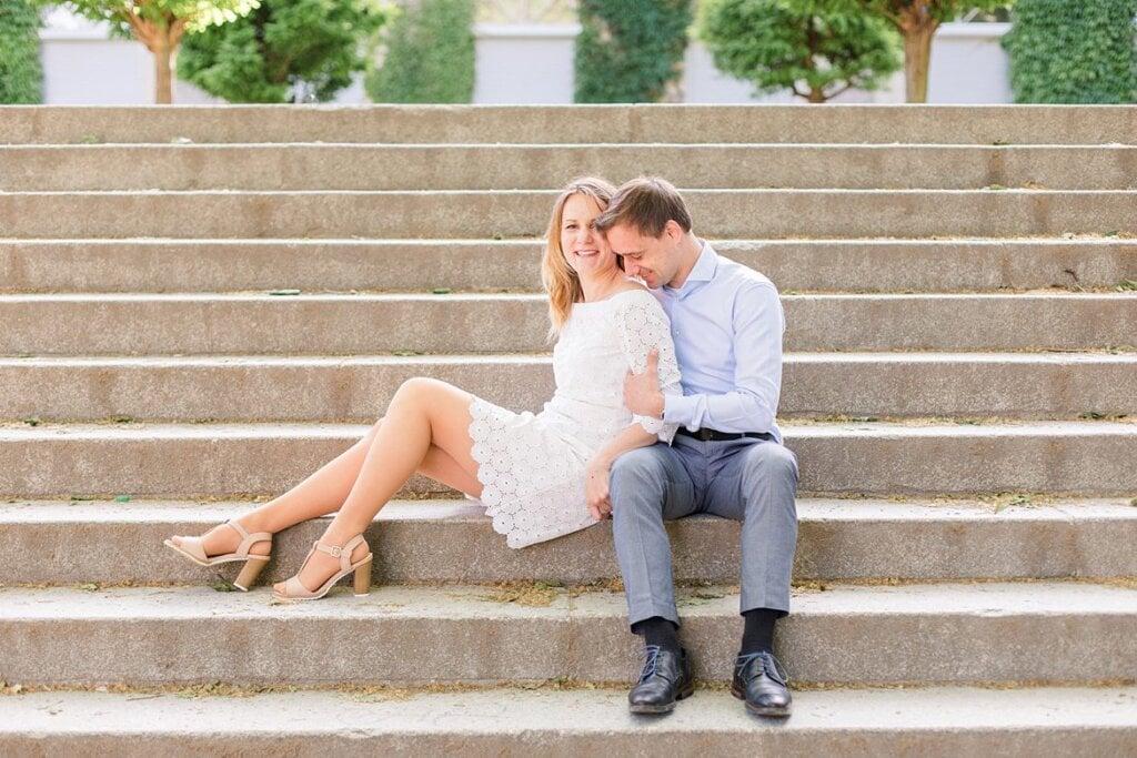 Pärchen sitzt auf einer Treppe. Er küsst ihre Schultern.