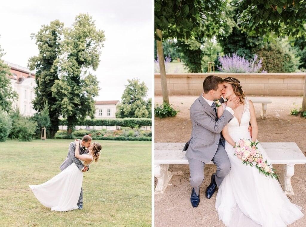 Brautpaar küsst sich im Park und sitzt auf Parkbank