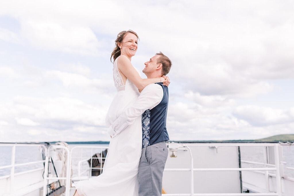 Bräutigam hebt Braut auf einem Schiff