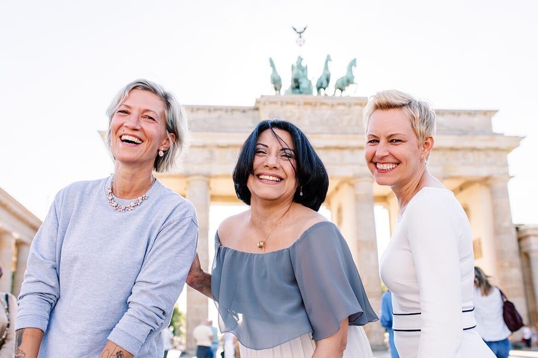 Drei Frauen lachen in die Kamera vor dem Brandenburger Tor Berlin