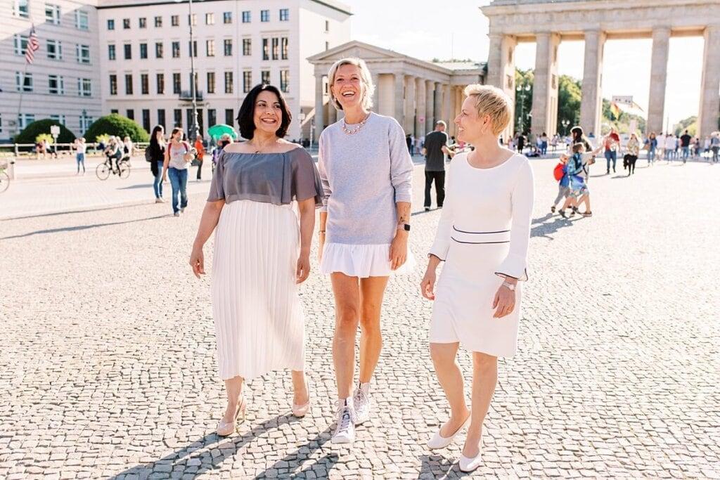Drei Frauen laufen vor dem Brandenburger Tor Berlin