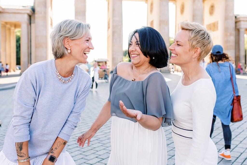Drei Frauen lachen vor dem Brandenburger Tor Berlin