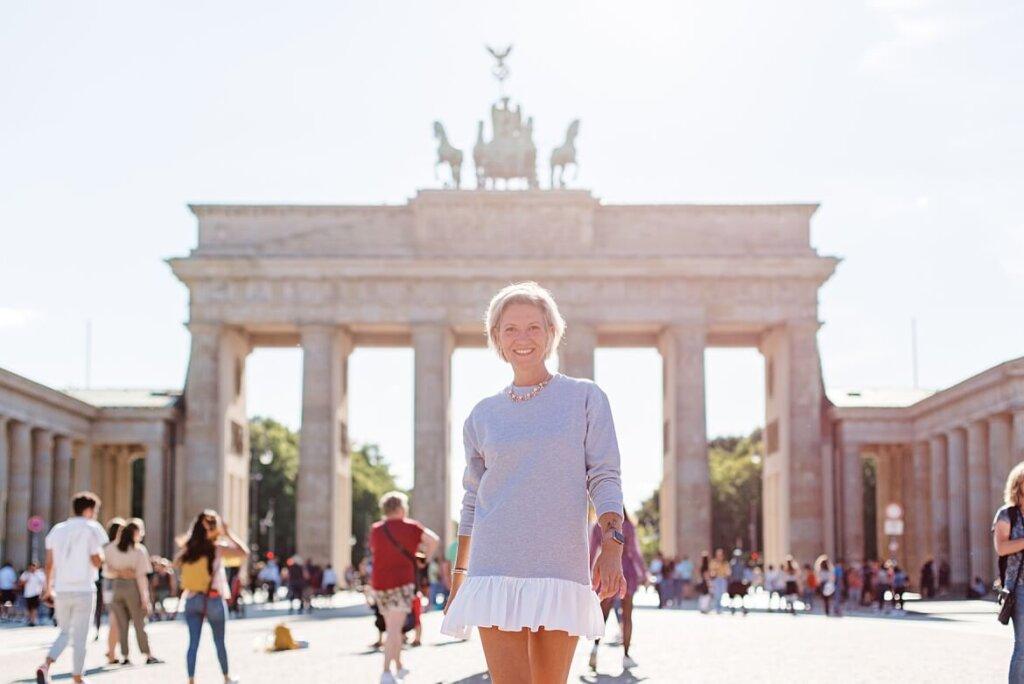 Eine Frau läuft vor dem Brandenburger Tor angestrahlt von der Sonne