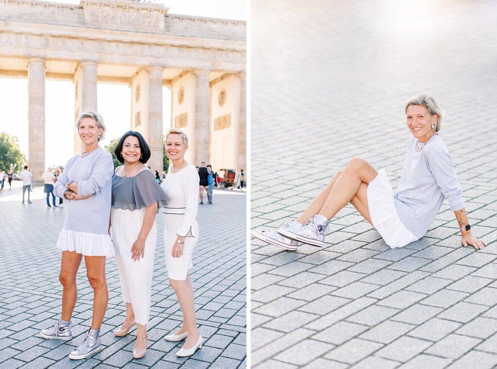 Drei Frauen stehen bzw. eine Frau sitzt vor dem Brandenburger Tor Berlin