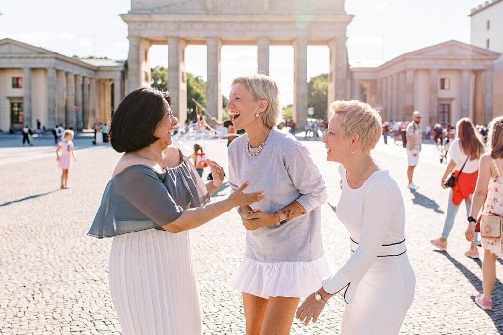 Drei Frauen schauen sich an und lachen vor dem Brandenburger Tor Berlin