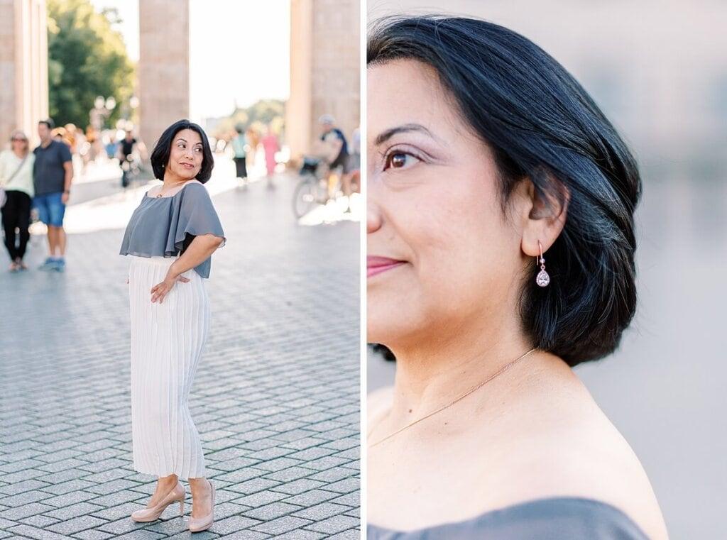 Eine Frau im grauen Oberteil und schwarzen Haaren vor dem Brandenburger Tor Berlin