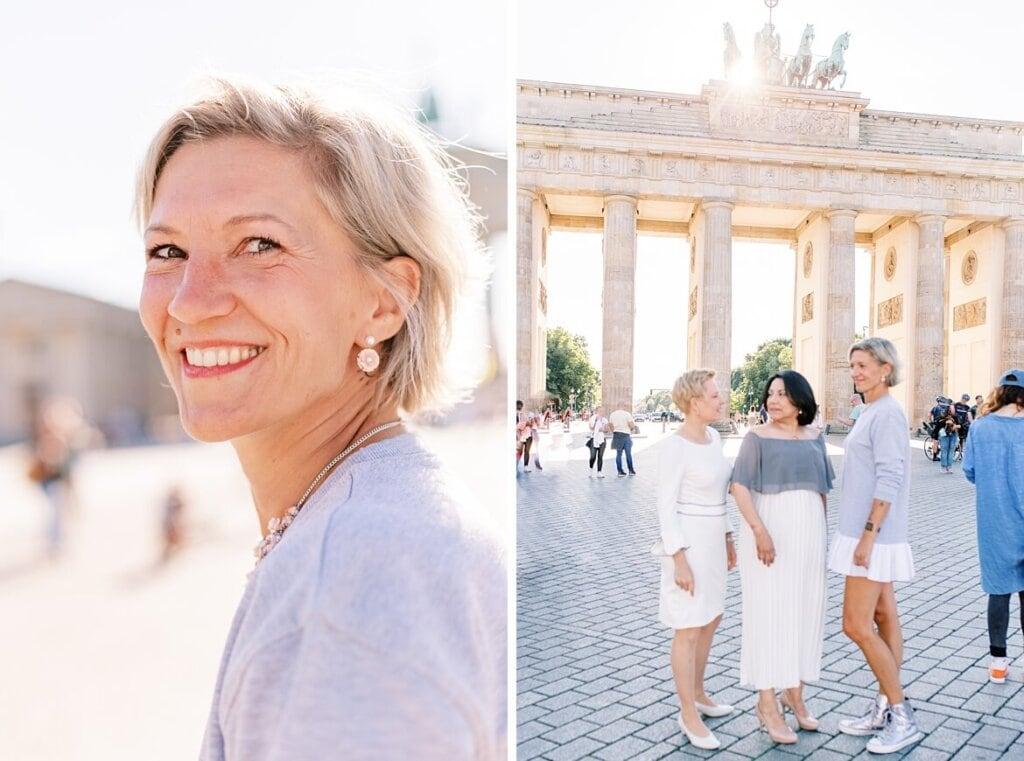 Eine Frau mit blonden Haaren schaut lachend in die Kamera. Drei Frauen verschwommen vor dem Brandenburger Tor Berlin