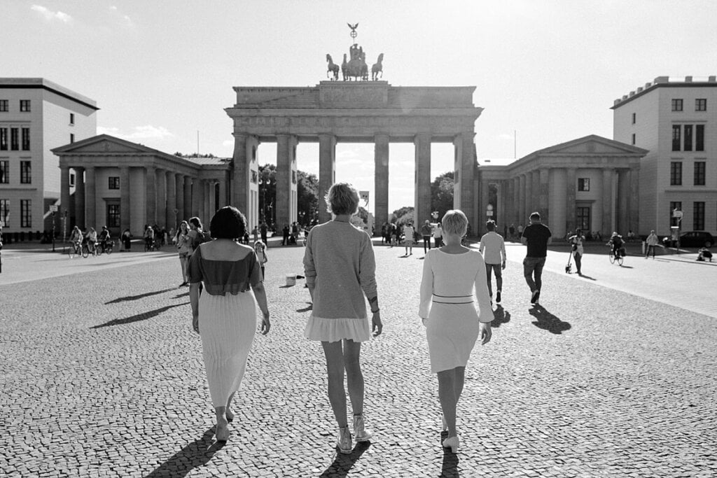 Schwarz Weiß Aufnahme von drei Frauen, die zum Brandenburger Tor Berlin laufen