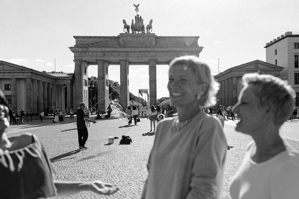 Schwarz weiß Foto von verschwommenden Frauen im Vordergrund und dem Brandenburger Tor Berlin im Hintergrund