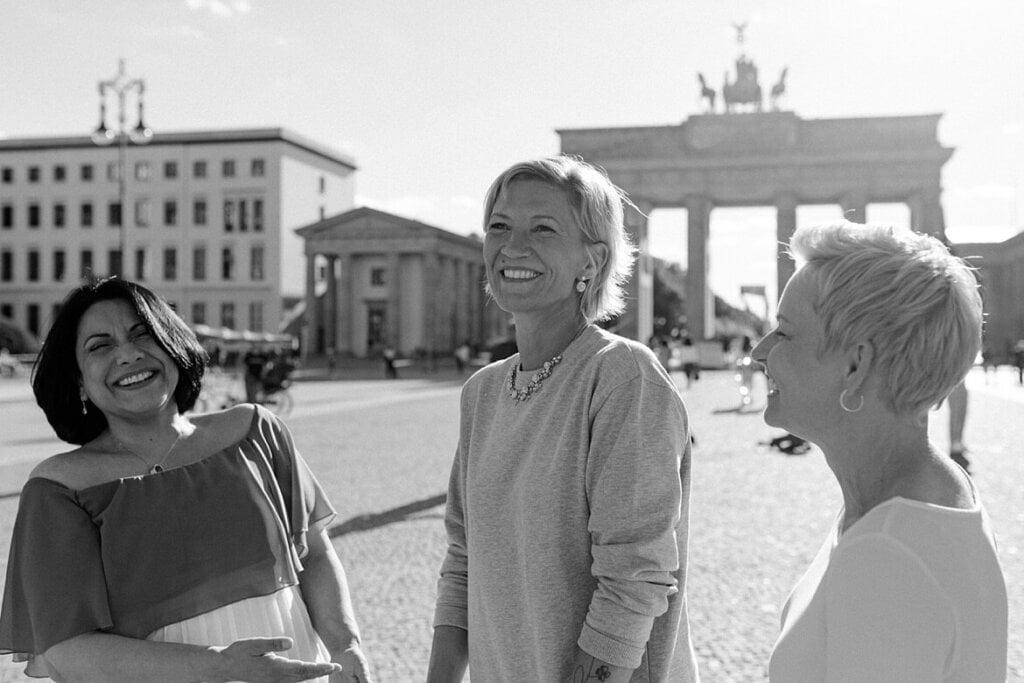 Schwarz weiß Foto von drei lachenden Frauen vor dem Brandenburger Tor Berlin