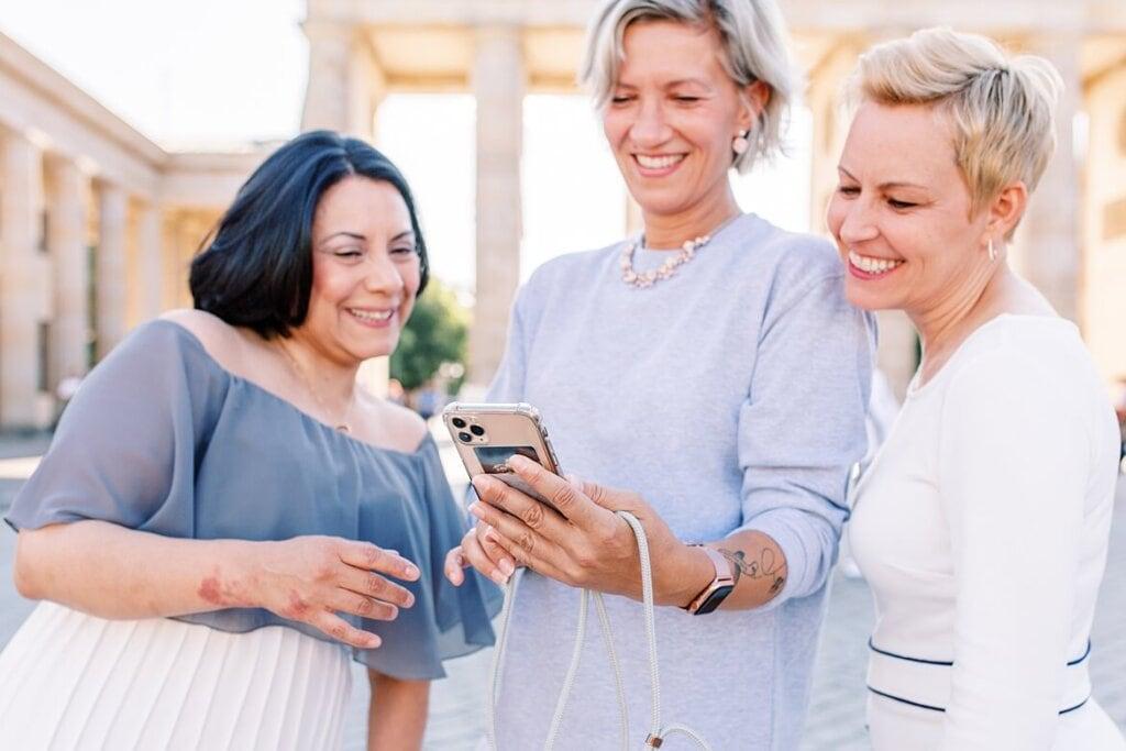 Drei Frauen schauen lachend auf ein Handy, im Hintergrund das Brandenburger Tor Berlin