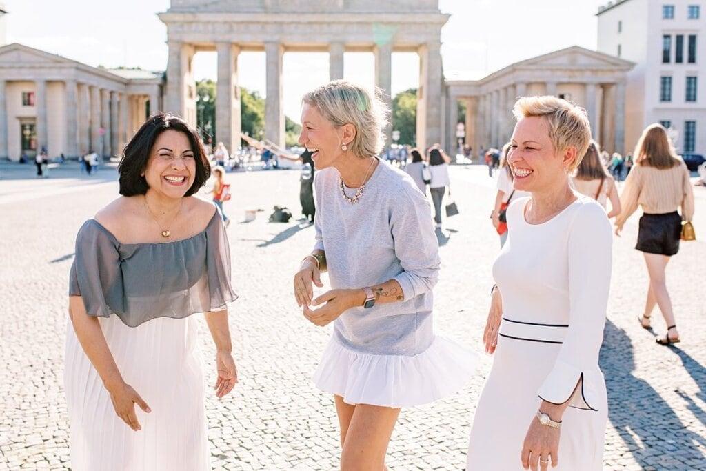 Drei Frauen lachen gemeinsam vor dem Brandenburger Tor Berlin