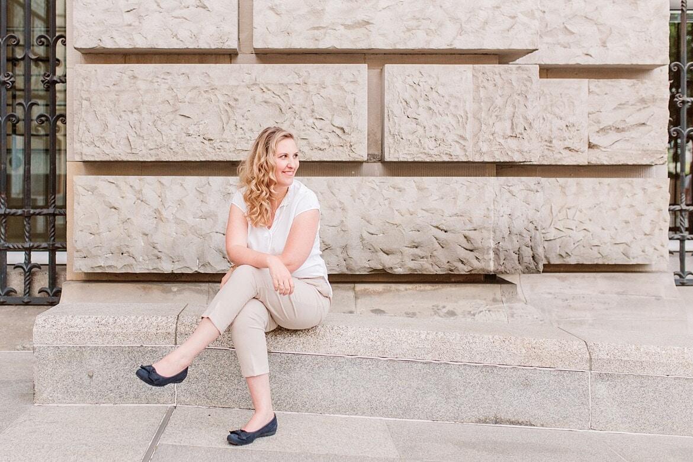 Frau sitzt auf Sandstein