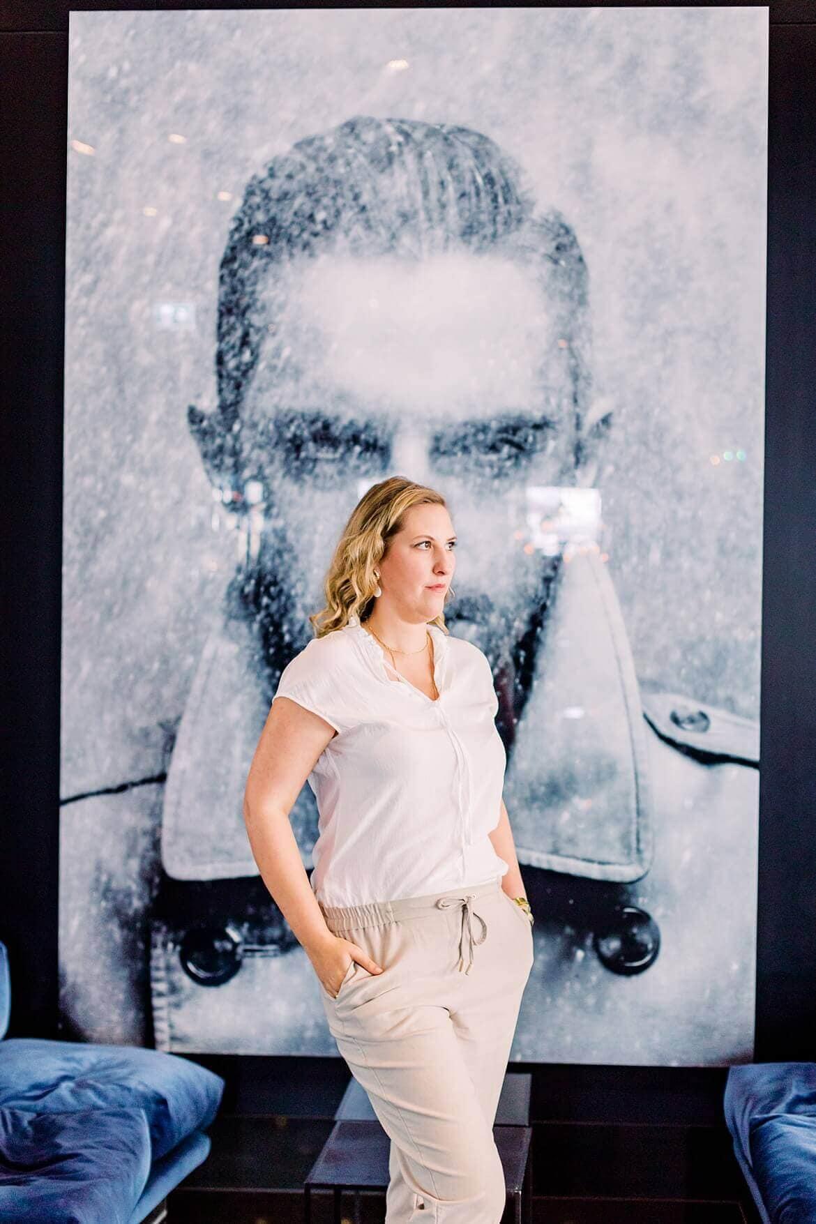 Frau steht vor einem Foto eines Mannes und schau zur Seite