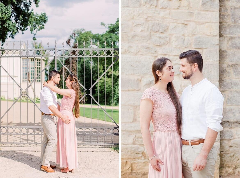 Verliebtes Paar vor Eisenzaun und Mauer