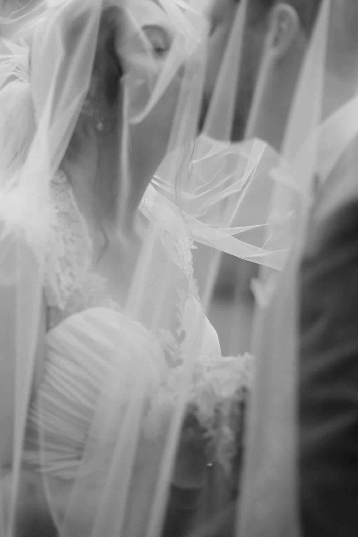 Schwarz Weiß Foto von Brautpaar unter Schleier