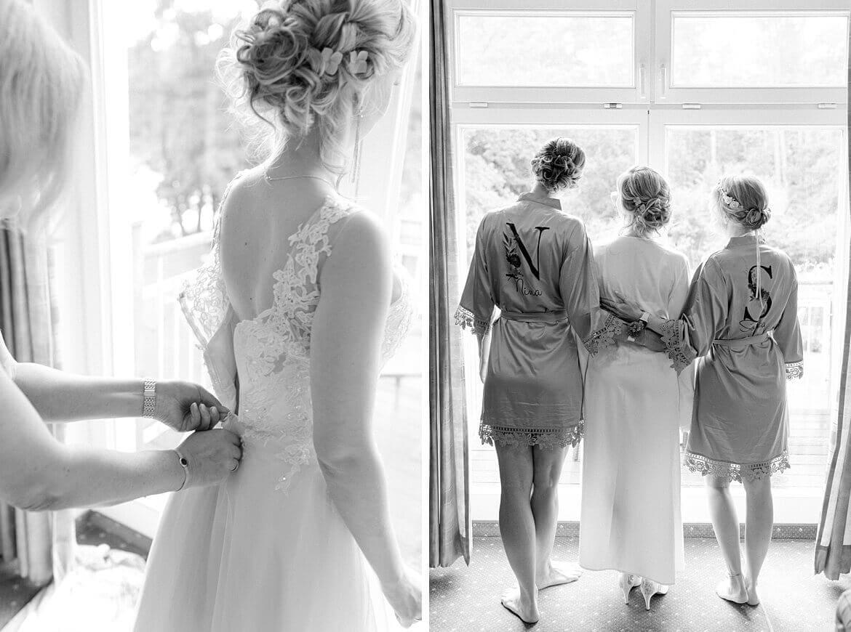 Brautmutter hilft Braut im Brautkleid und Trauzeuginnen und Braut in Roben